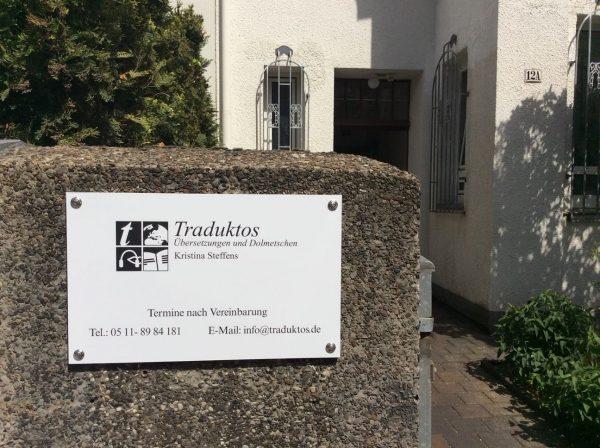 Weißes Firmenschild mit schwarzem Text: Traduktos - Übersetzungen und Dolmetschen